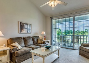 living room with ceiling fan, couch, coffee table, and views of the golf course and balcony, myrtle beach pet friendly vacation rental home