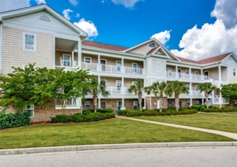 large 3 story apartment building with grass lawn infront, myrtle beach pet friendly vacation rental home